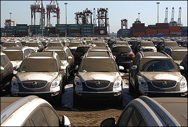Dust-covered SUVs lie in a port.