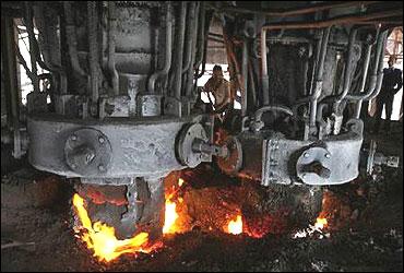 An employee works inside a steel factory.