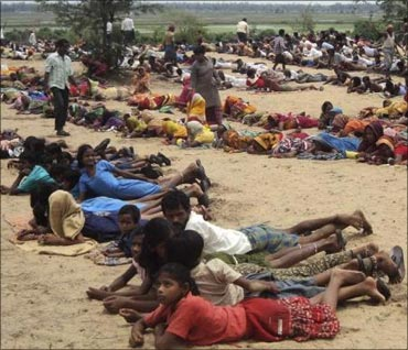 Villagers and their children lie at the proposed site of a $12-billion steel plant by South Korea's Posco during a protest in Orissa on June 11.