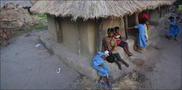 Children gather at the entrance of their thatched hut in Gobindpur village.