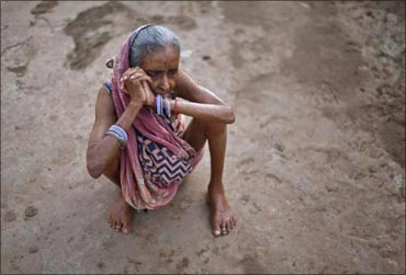 A woman sits on the ground at a transit camp for villagers who have been displaced in Jagatsinghpur.