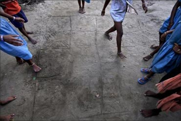 Children play a game of hopscotch on a grid drawn into the dirt in Gobindpur village.