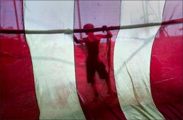 A man is seen silhouetted through fabric as he constructs a temporary shelter at a transit camp.