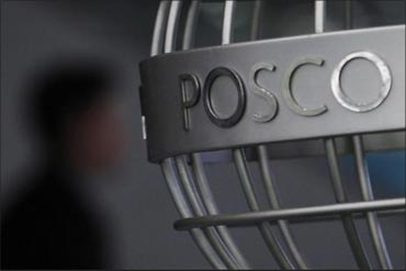 A man walks past a Posco logo.