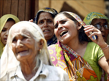 Women weep after police arrested their family members, following clash between farmers and police.