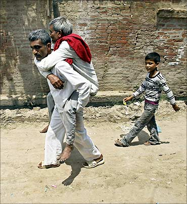 A villager carries an injured man to a hospital after farmers clashed with police.