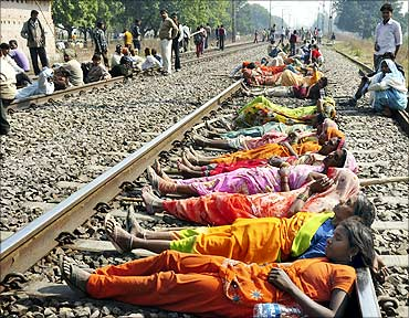 Farmers block railway tracks during a protest in Karchana town in UP.