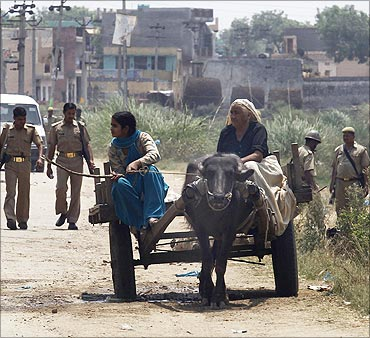Police patrol as villagers ride past in a buffalo cart in UP.