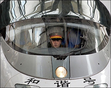 A train driver sits in a new high-speed train before it departs from Beijing-South railway station.