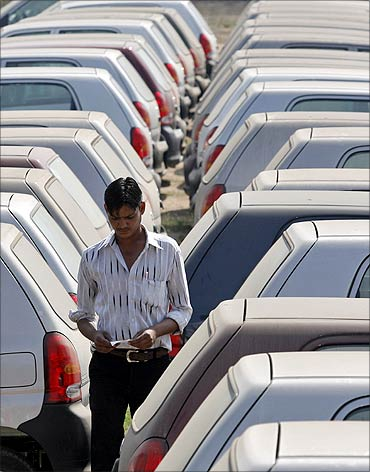 An employee walks between parked cars at Maruti Suzuki's stockyard.
