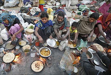 Homeless people prepare food on a roadside in Ahmedabad.