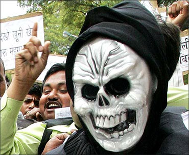 An Indian trader wears a mask during a protest against the Value Added Tax (VAT),