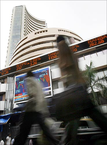 People walk pass the Bombay Stock Exchange building displaying Sensex.
