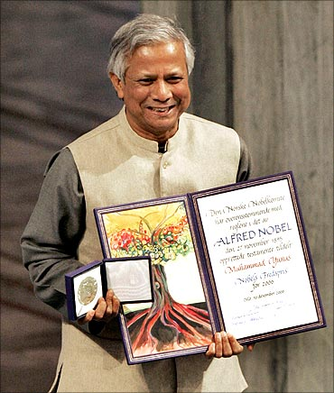 Nobel Peace Prize winner Muhammad Yunus of Bangladesh poses with his award during a ceremony at the city hall in Oslo.