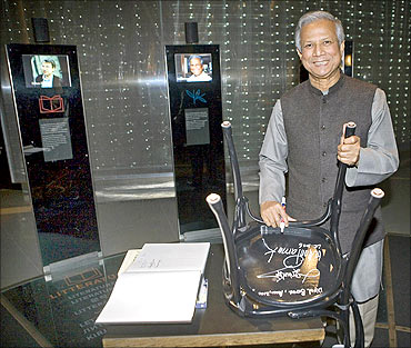 Muhammad Yunus signs the bottom of a chair whilst visiting the Nobel Museum in Stockholm.