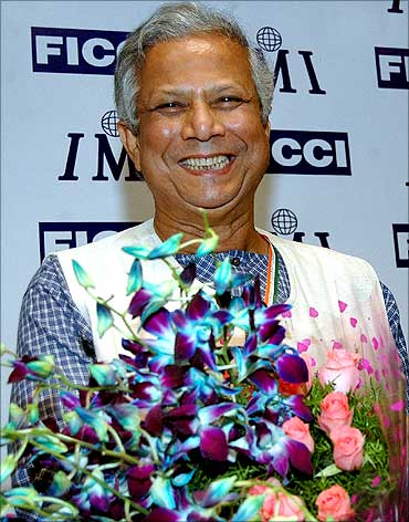 Dr Muhammad Yunus carries a bouquet of flowers presented at Ficci in New Delhi.