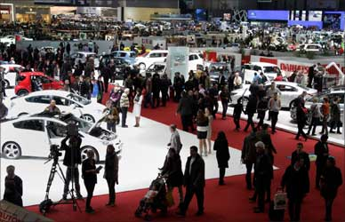Visitors stroll through the stands on the first day of the 81st Geneva Motor Show at the Palexpo in Geneva.