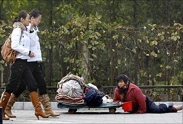 A woman begs on a road in the embassies district of Beijing.