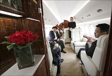 Mainland Chinese visitors sit inside a Dassault Falcon 7X business jet.