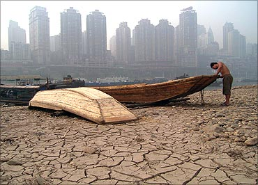 A boatman repairs his boat on the dried-up riverbed of the Jialing River.