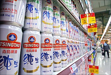 A customer walks past Tsingtao beer cans at a supermarket in Nanjing.