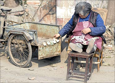 An elderly woman counts small yuan notes on a street in Xiangfan, central China's province.