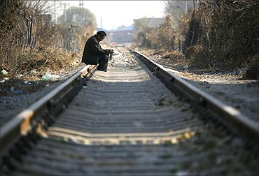 A Chinese man sits on train tracks in a rundown area located on the outskirts of Beijing.