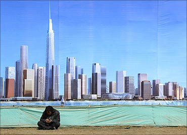 A worker rests in front of an artist's impression of the new business district of Binhai.