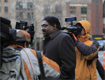 Rajaratnam outside the court house surrounded by media.