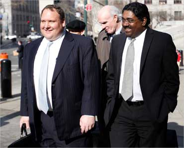 Galleon hedge fund founder Raj Rajaratnam (R) leaves federal court after a hearing in New York.