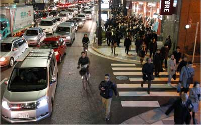 Residents walk between grid locked vehicles on their way home among chaotic traffic in central Tokyo