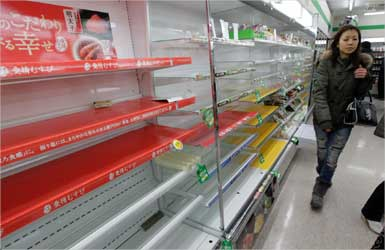 woman looks for supplies in a store in Tokyo that has almost sold out of food and drinks.