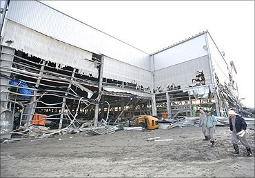 Workers walk past a damaged shipyard in an area hit by an earthquake and tsunami in Kuji.