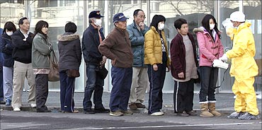People queue to be screened by a technician in protective gear for signs of possible radiation.