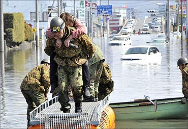 A woman is rescued from a flooded area by Japan Self Defense Forces troops.