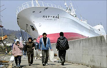 People walk in front of a tuna fishing boat tossed on to land in Kesennuma City.