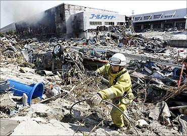 A firefighter walks around rubble near a burning factory damaged by an earthquake.