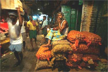 A potato seller smokes outside his shop at a vegetable wholesale market in Kolkata.