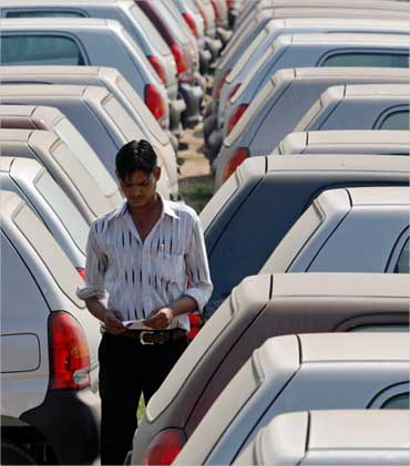 An employee walks between parked cars at Maruti Suzuki's stockyard on the outskirts of Ahmedabad.