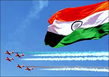 The Indian flag flutters as Indian Air Force jets fly by.