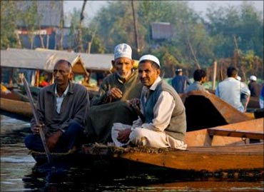 Kashmiris sitting by the Dal Lake on a shikara.
