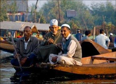 Kashmiris sitting by the Dal Lake on a shikara.