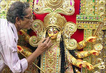 A sculptor gives finishing touches to an idol of Goddess Durga in Kolkata.