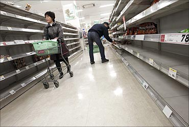 People shop for food from almost empty shelves at a big-box supermarket in Tokyo.