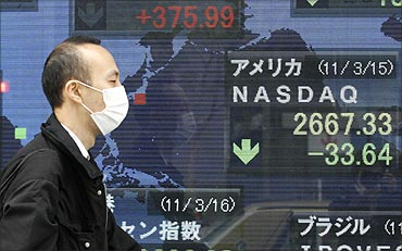 A man wearing a mask walks past an electronic board displaying the Nasdaq average.