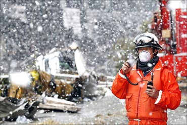 A rescue worker uses a two-way radio transceiver during heavy snowfall at a factory area.