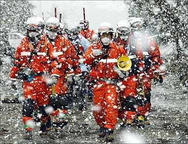 Rescue workers walk in heavy snowfall at a factory area that was devastated by earthquake.