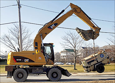 A Caterpillar tractor lifts a piece of construction equipment in Somerville, Massachusetts.