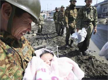 A Japan Self-Defense Forces officer holds a 4-month-old baby girl who was rescued along with her family members from their home in Ishimaki City.