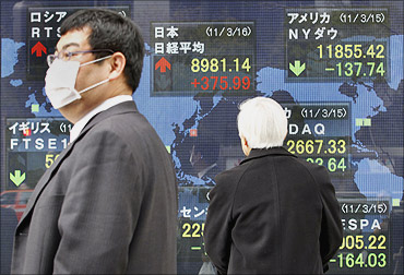 A man wearing a mask walks past an electronic board displaying movements in various market indices around the world, in Tokyo.